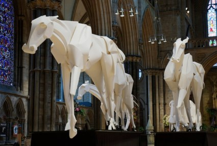 The horses are made of flexible wooden frames that are covered with paper