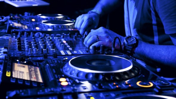 dj hands on the mixing table in blue light
