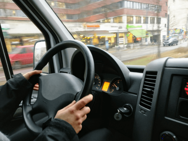 person holding steering wheel while driving