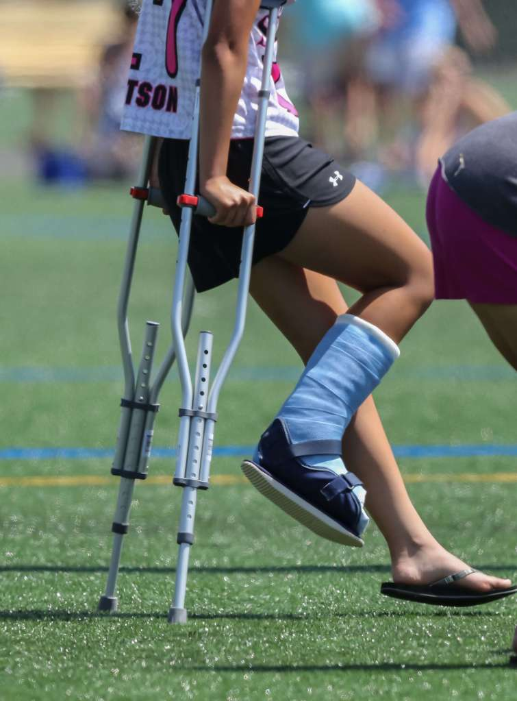 Girls lacrosse player walking with crutches with a right broken ankle in a boot - overuse injury from early recruiting for college lacrosse © Equity IX - SportsOgram - Leigh Ernst Friestedt
