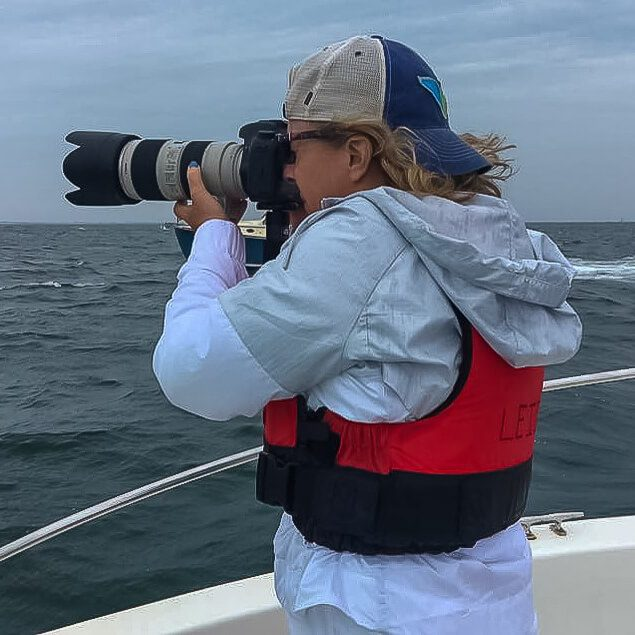 Leigh Ernst Friestedt - CEO Equity IX - SportsOgram - taking a picture on a boat with a camera, red life jacket and hat on backwards