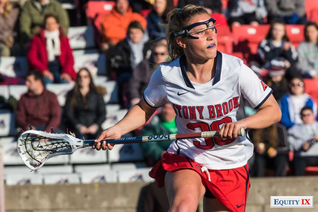 #30 Ally Kennedy midfield for Stony Brook holds lacrosse stick with sun on her face with goggles © Equity IX - SportsOgram - Leigh Ernst Friestedt - ZyGoSports