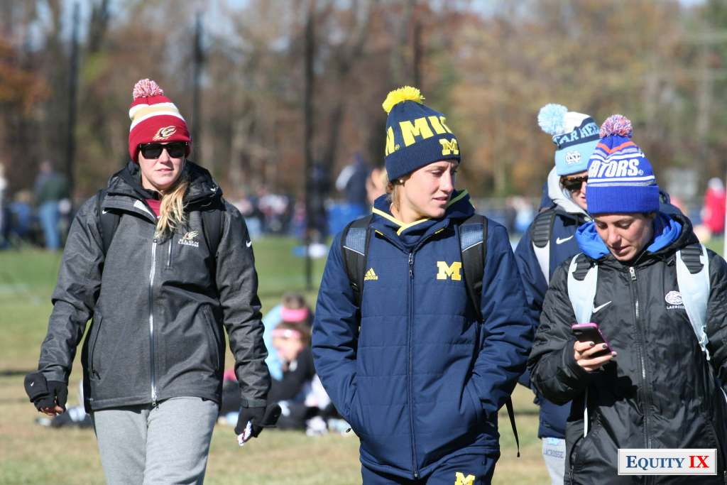 Michigan and Florida women's lacrosse coaches walk on a cold day at an early recruiting tournament wearing winter hats and jackets with their college logos on them. Photo by Leigh Ernst Friestedt © Equity IX - SportsOgram