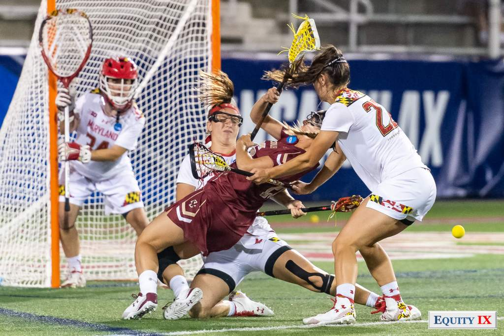 Two Maryland defender sandwich and cross check Boston College attacker at 2018 NCAA Women's Lacrosse Final Four - players are wearing knee braces and falling onto the turf © Equity IX - SportsOgram - Leigh Ernst Friestedt