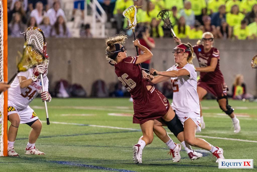 Maryland defense #25 Lizzie Colson cross checks Boston College #26 Cara Urbank wearing a knee brace and going to goal - 2018 NCAA Women's Lacrosse Final Four © Equity IX - SportsOgram - Leigh Ernst Friestedt