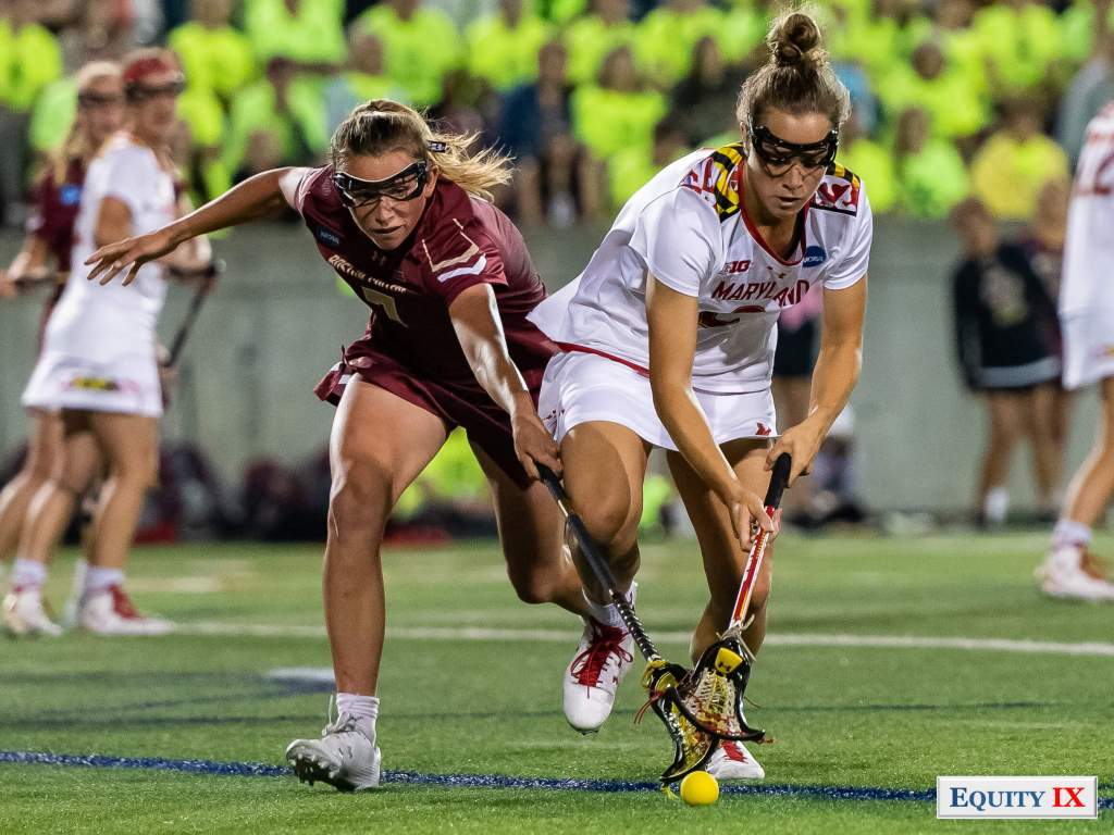 Two female lacrosse players battle for a ground ball with their lacrosse sticks on the turf - Boston College vs Maryland - 2018 NCAA Women's Lacrosse Final Four © Equity IX - SportsOgram - Leigh Ernst Friestedt