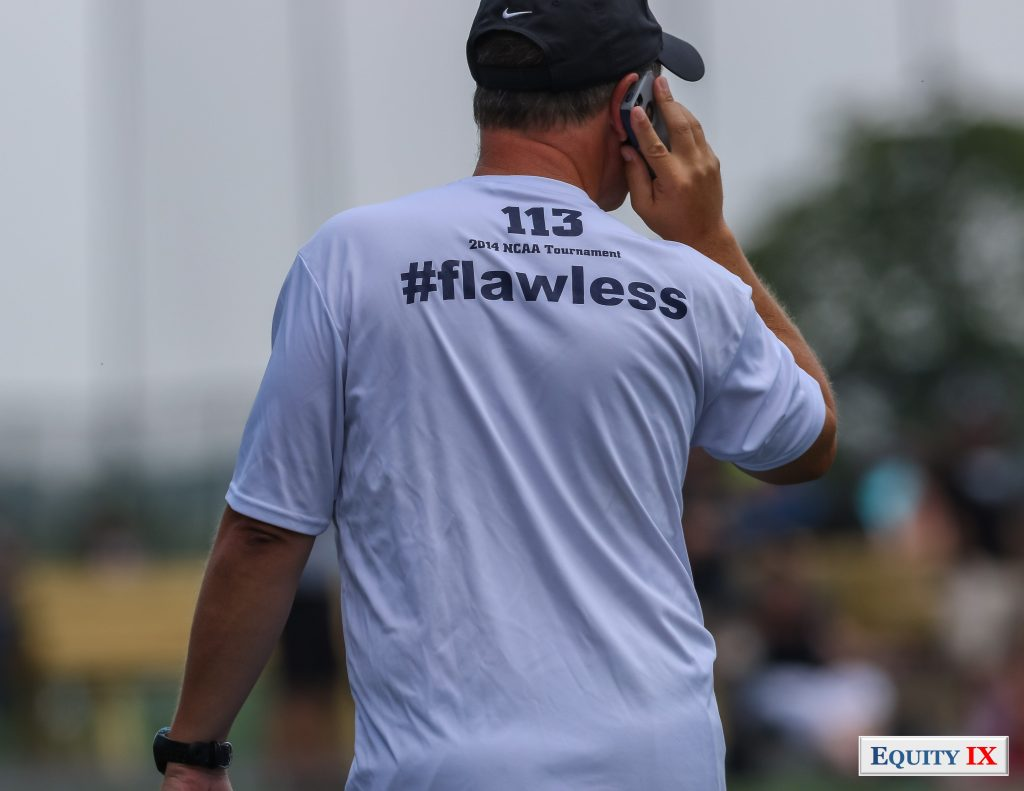 "Ricky Fried - Georgetown Women's Lacrosse Head Coach on the phone at early recruiting girls club lacrosse tournament wearing a ""flawless"" 2014 NCAA Tournament t-shirt and Nike baseball hat © Equity IX - SportsOgram - Leigh Ernst Friestedt"