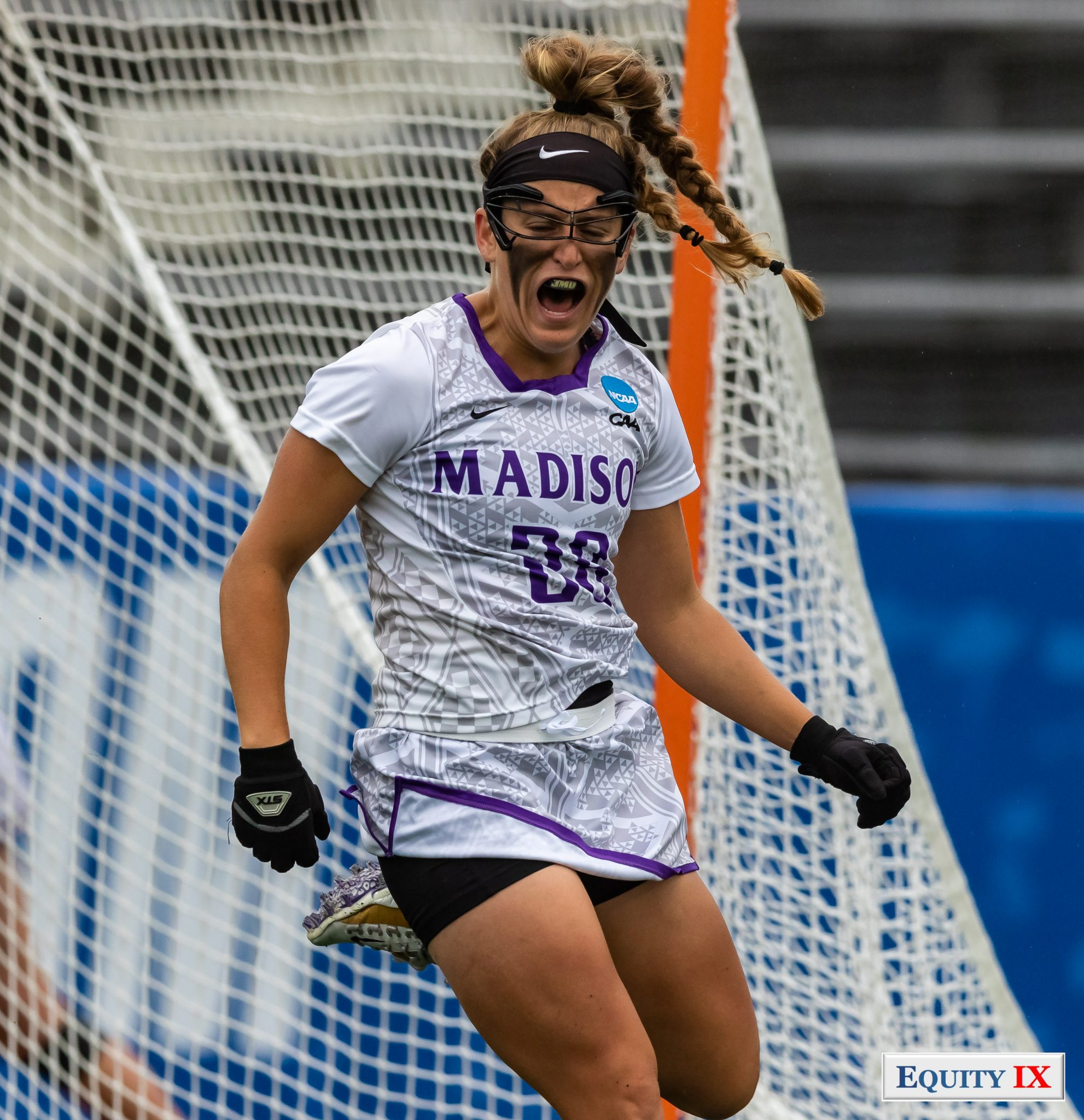 Elean Romesburg (JMU #28) celebrates scoring a goal at 2018 NCAA Women's Lacrosse Championship Game wearing goggles, eye black and black gloves © Equity IX - SportsOgram - Leigh Ernst Friestedt