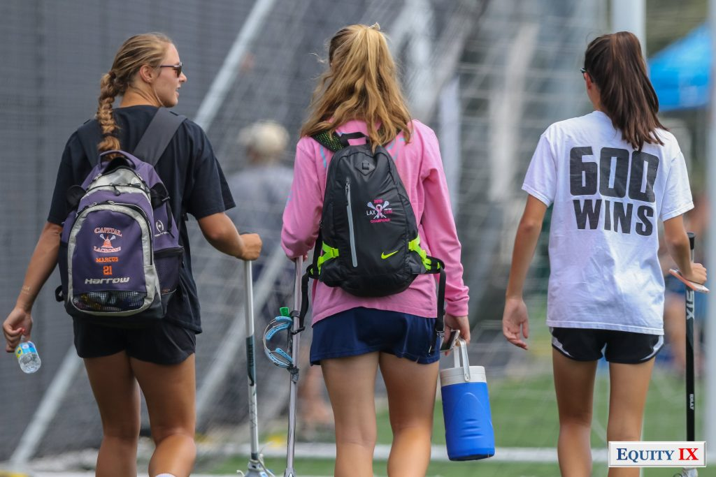 Early recruits from DC Capital Girls Club lacrosse team walk off the field with their lacrosse sticks - Olivia Pugh wears a white t-shirt with 600 wins on the back referencing 600 wins at her high-school St. Stephens & St. Agnes - Jordan Marcus and the other girls are wearing lacrosse back packs - 2015 Girls Club Lacrosse - Nike Elite G8 © Equity IX - SportsOgram - Leigh Ernst Friestedt
