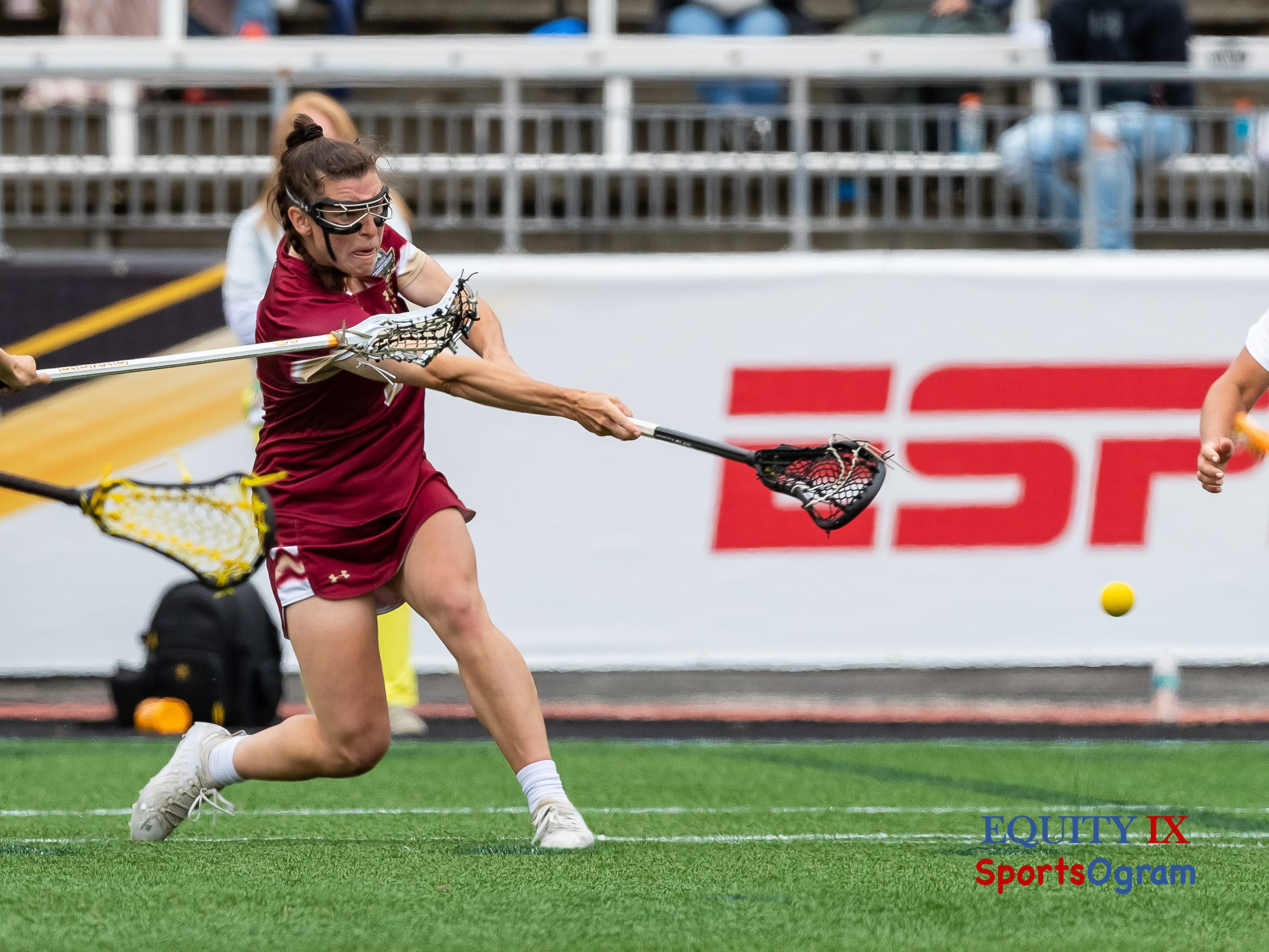 #8 Charlotte North (Boston College) shoots lacrosse ball by extending her black lacrosse stick right handed with muscles in arm and yellow ball firing out of the stick in the air - 2021 NCAA Women's Lacrosse Championship Game © Equity IX - SportsOgram - Leigh Ernst Friestedt
