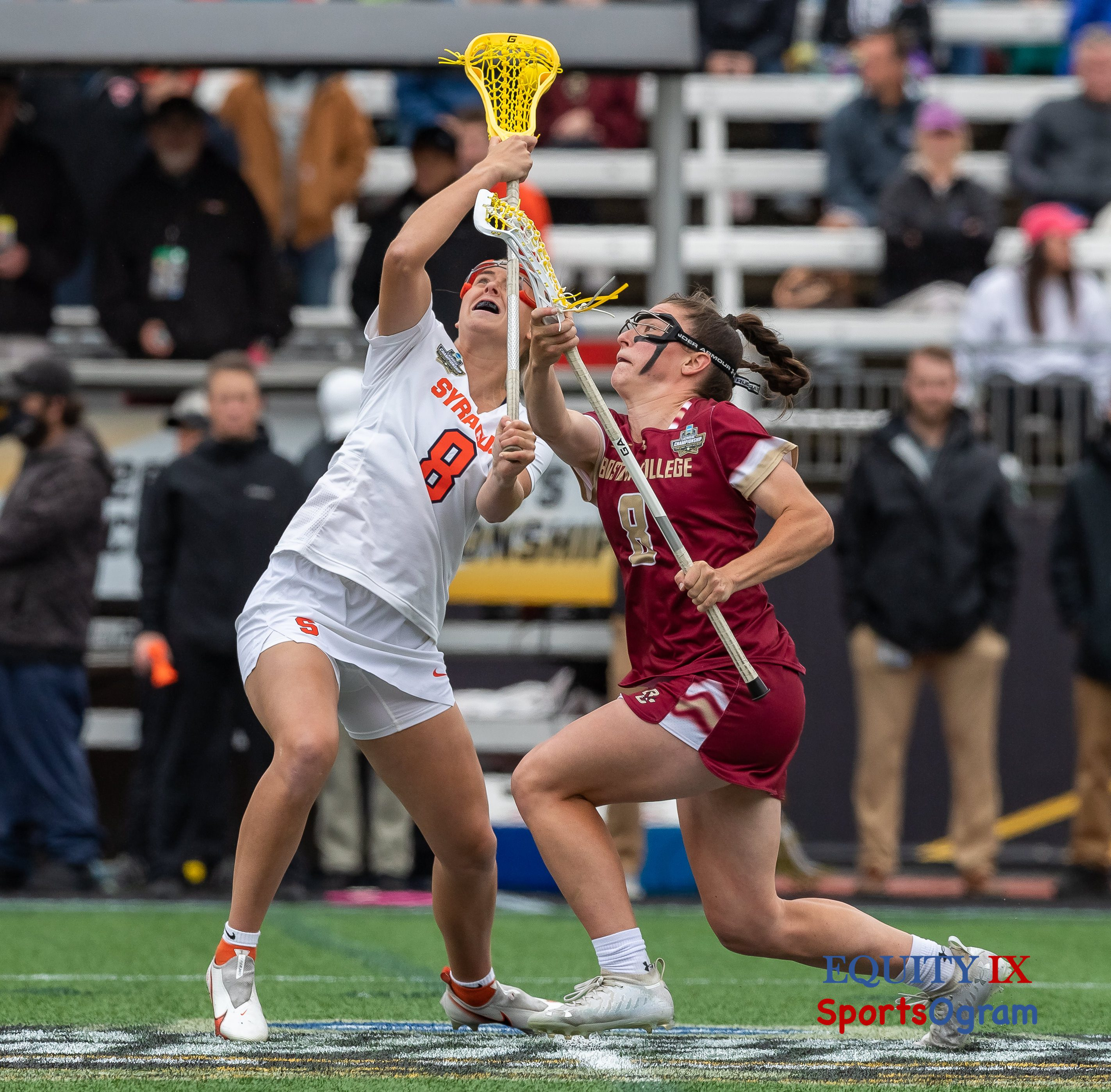 Two female lacrosse players draw a yellow lacrosse ball to start the 2021 NCAA Women's Lacrosse Championship Game - #8 Charlotte North (Boston College) vs #8 Syracuse - the yellow lacrosse ball is on the yellow strings of Syracuse player and flipping backwards over her shoulder © Equity IX - SportsOgram - Leigh Ernst Friestedt