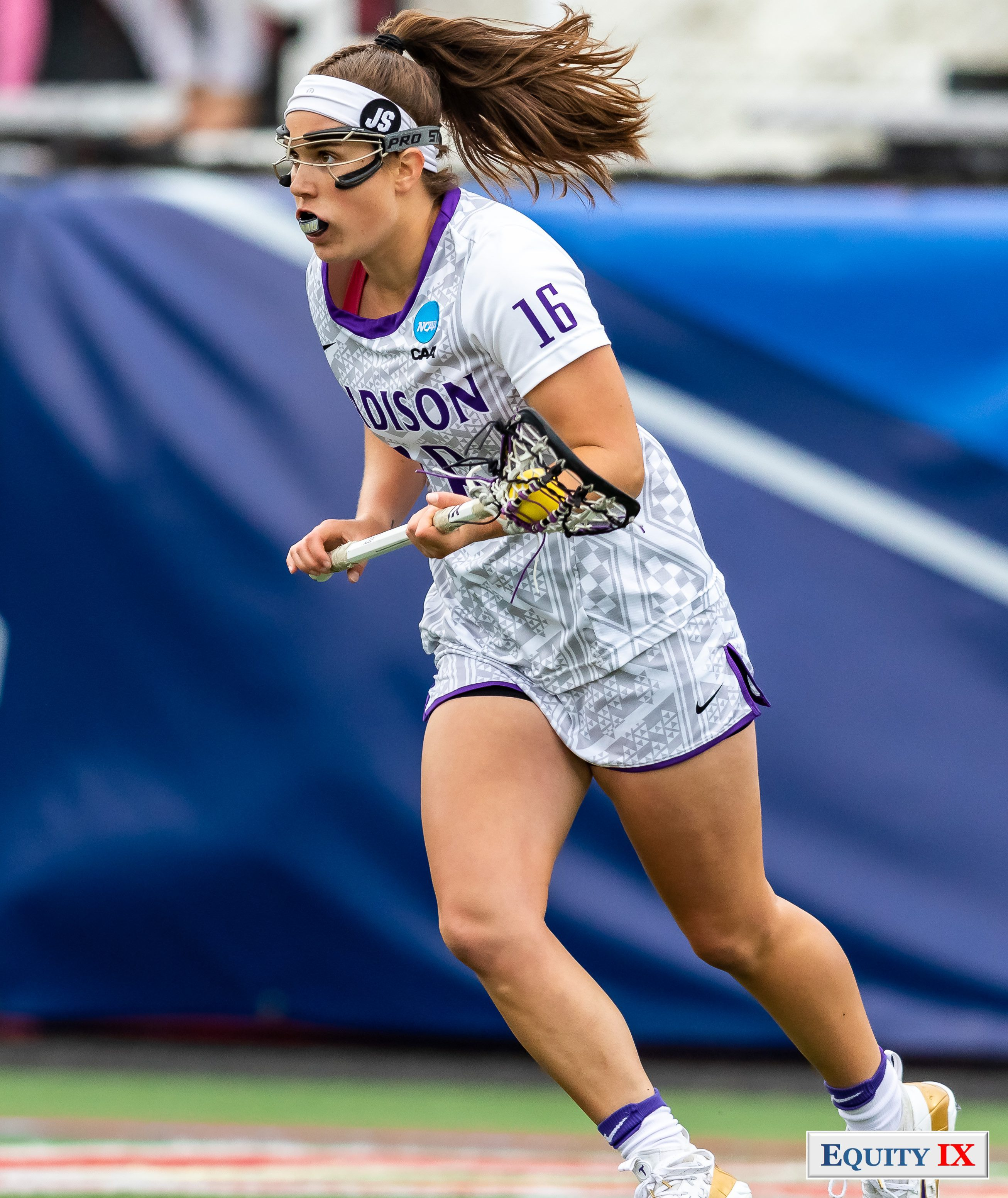 """#16 Corinne Schmidt (JMU) cradles yellow lacrosse ball in her stick left handed and runs down the field wearing a white headband with the initial """"JS"""" on the side, googles and mouthguard - 2018 NCAA Women's Lacrosse Champions © Equity IX - SportsOgram - Leigh Ernst Friestedt"""