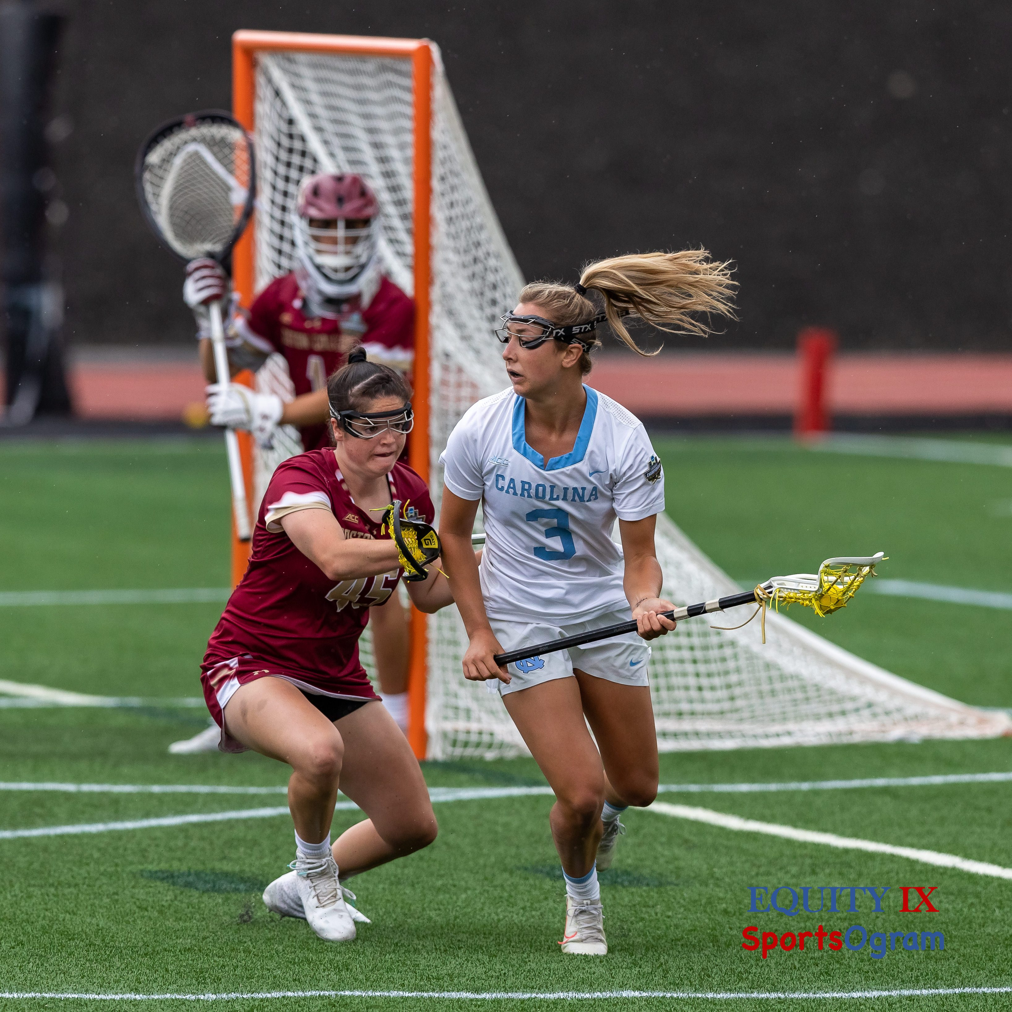#3 Jamie Ortega (UNC) looks to pass lacrosse ball but is tightly defended by #45 Sydney Scales (Boston College) cross checking Jamie's right arm and forcing her away from the goal - 2021 NCAA Women's Lacrosse Final Four © Equity IX - SportsOgram - Leigh Ernst Friestedt