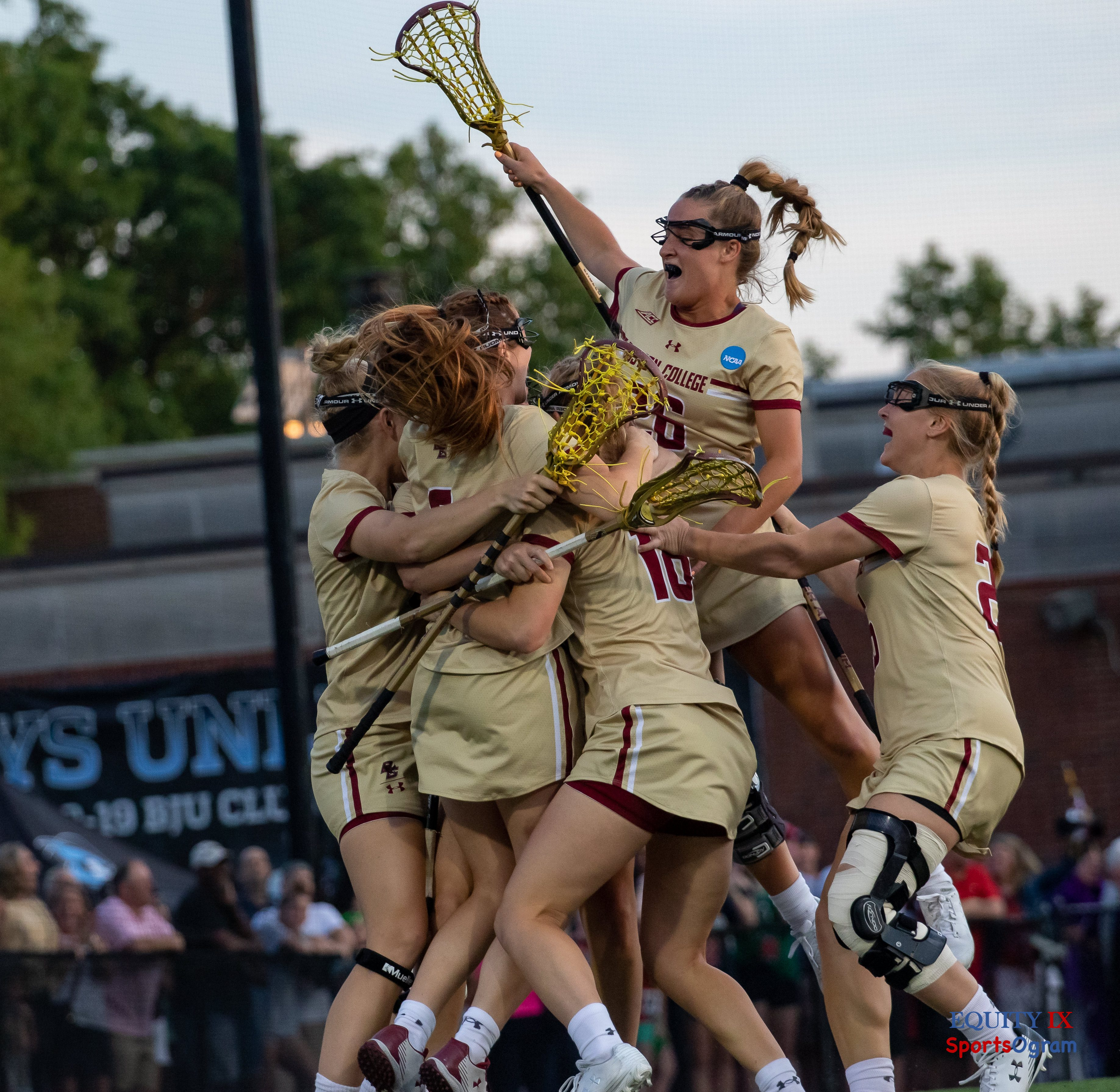 Boston College women's lacrosse team celebrates after #2 Sam Apuzzo scores winning goal in overtime - #26 Cara Urbank (Boston College) soars above all of the other players with her lacrosse extended and braided ponytail - 2019 NCAA Women's Lacrosse Final Four © Equity IX - SportsOgram - Leigh Ernst Friestedt