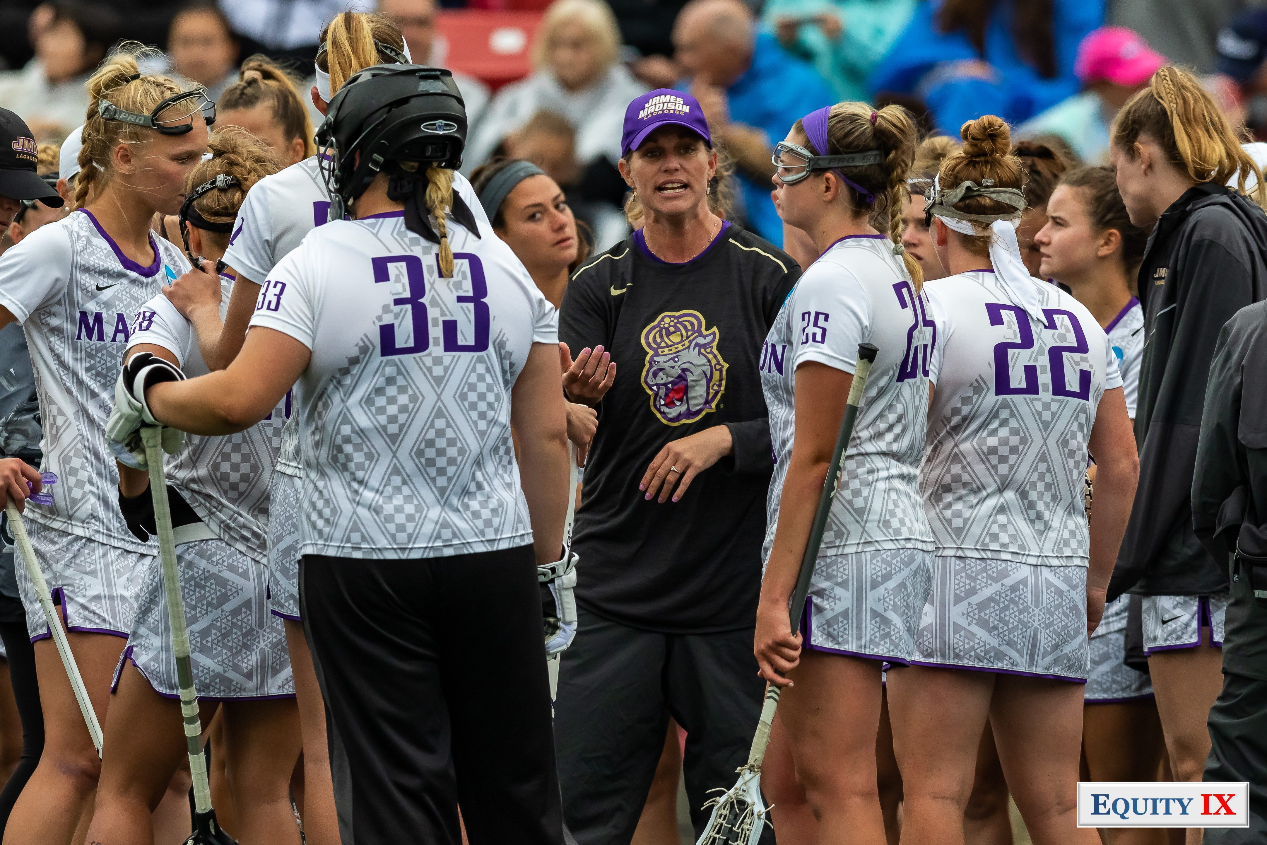 JMU Head Coach Shelley Klaes-Bawcombe speaks passionately to her team during a time out in a huddle featuring top players #33 goalie Molly Dougherty wearing black helmet, #25 Haley Warden and other female lacrosse players - Coach is wearing purple James Madison Lacrosse baseball hat with Duke sweatshirt - 2018 NCAA Women's Lacrosse Champions © Equity IX - SportsOgram - Leigh Ernst Friestedt