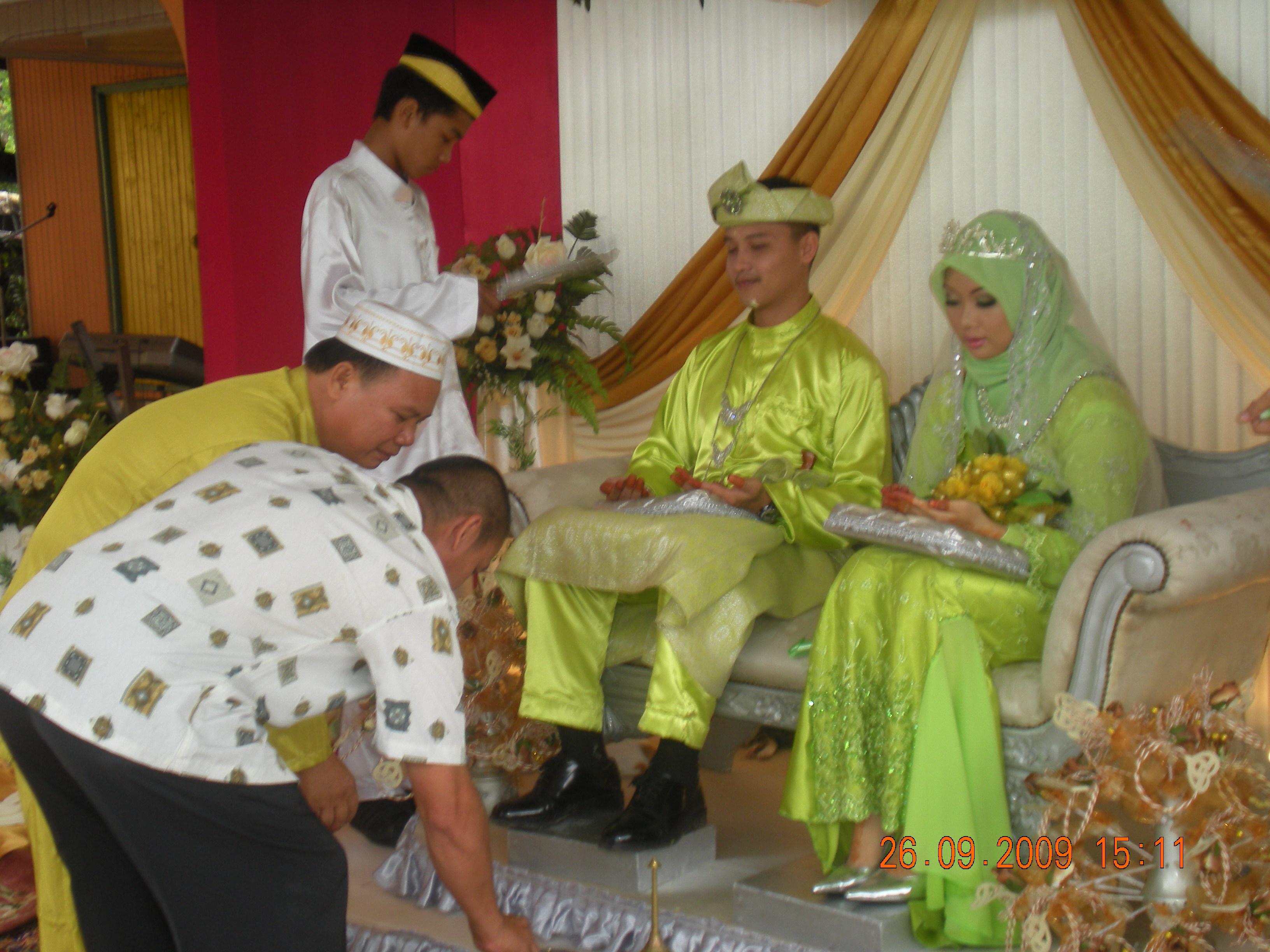 Mohd Jeffrin berbaju melayu kuning dan besannya En Risit, bapa kepada pengantin lelaki sedang melakukan renjisan kepada anak tersayang di pelamin. Kini sudah berbesan rupanya Cikgu jeffrin sekarang.