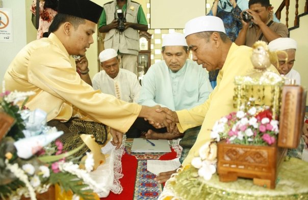 Hj Mohd Elham, ayah kandung (wali) kepada Eja melaksanakan sendiri akad nikah Ismael dengan puterinya Eja. Kelihatan Tuan Imam Daerah Kota Belud menyaksikan upacara tersebut