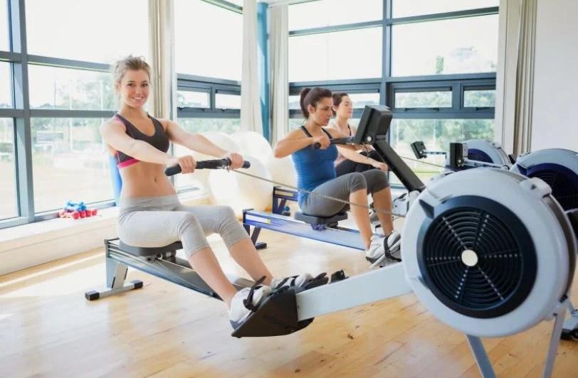 Usar la máquina de remo en el gimnasio.