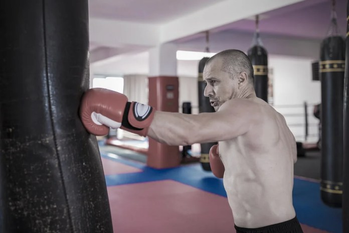 Hombre golpeando un saco de boxeo.