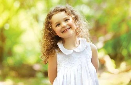 Niña sonriendo porque ha aprendido que la empatía y la sinceridad han de ir unidas.
