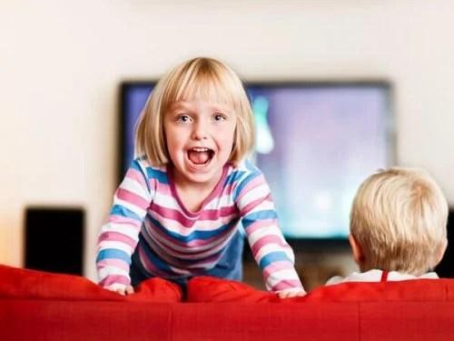 Niña con dificultades atencionales subida en el sofá dando voces.