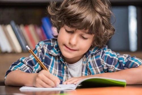 Niño escribiendo palabras nuevas en un cuaderno para detectar posibles síntomas de la disgrafía.