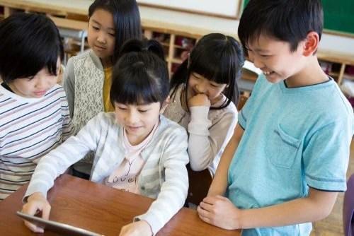 Niños en clase con una tablet usando algunas Apps infantiles para aprender ortografía.