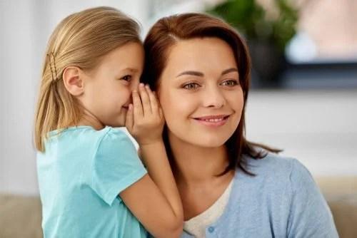 Madre escuchando lo que le dice su hija al oído sobre una experiencia con personas tóxicas.