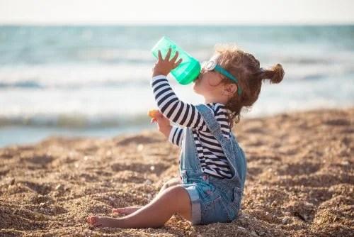 Niña en la playa bebiendo agua.