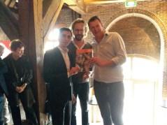 Wethouder Laudy (l) overhandigt de brochure aan Johan Klerks en Bob Meijer van Visbrasserie De Poort