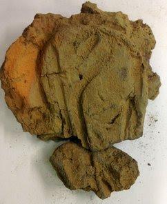Fragment met afdrukken van verschillende omgesmolten voorwerpen, waaronder een mantelspeld. Foto: RCE