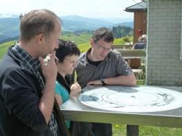 Sven, Bernadette und Dietmar studieren das Bergpanorama