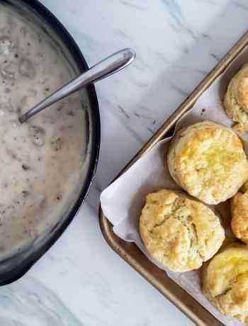 The BEST homemade Southern Biscuits and Sausage Gravy Recipe! This recipe is easy, makes plenty for a crowd and perfect for breakfast or brunch. The biscuits are flaky and made from scratch. The Gravy is made with ground sausage and milk! Classic and simple!