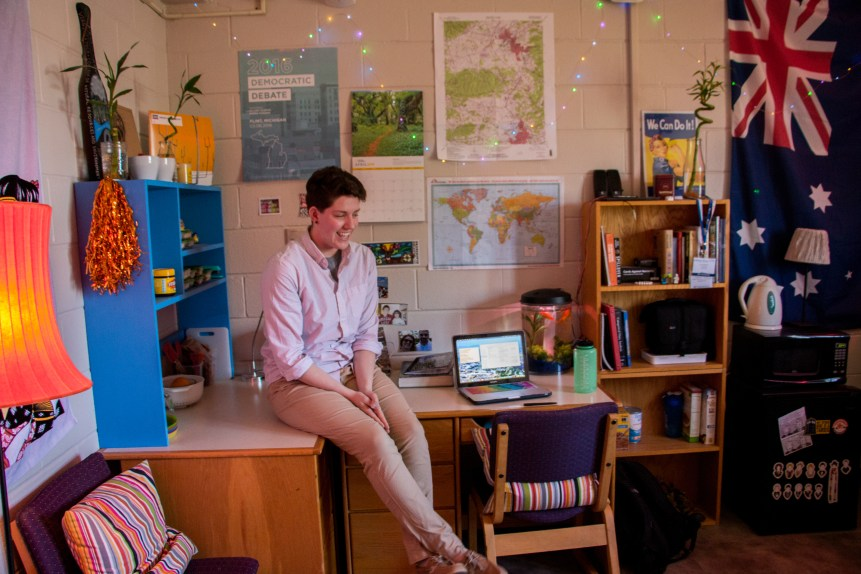 In the photo, a young woman (Maggie Carolan) sits on a desk in her dorm room. Her wall is covered with decorative posters, string lights, and a hanging Australian flag.
