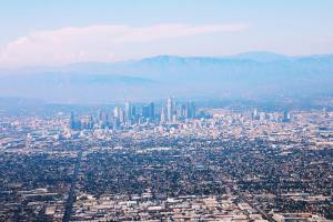 A photo taken from a plane overlooking the Los Angeles skyline, which appears in vivid pink and blue hues.