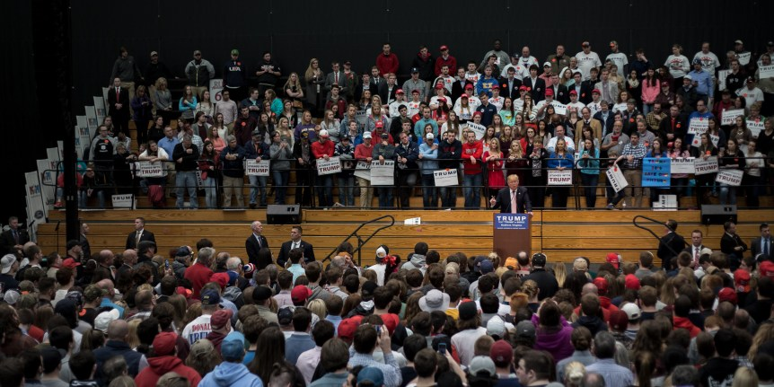 In the photo, soon-to-be President Donald Trump stands on a platform and speaks in front of a massive crowd of people.