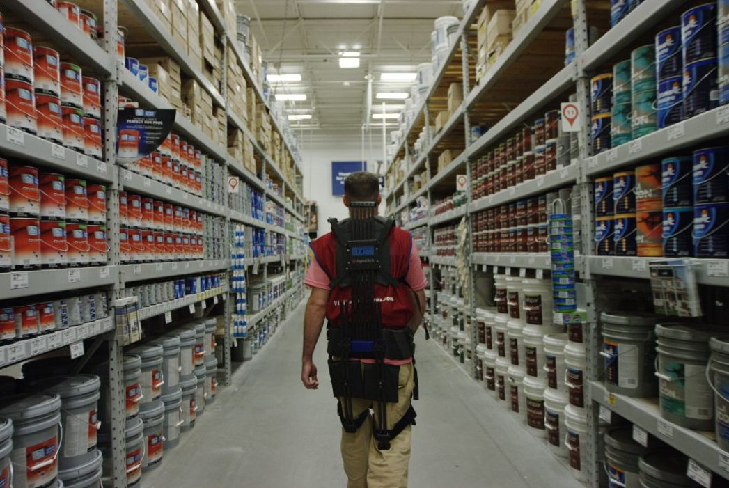 A man wears a soft robotic suit through an isle in Lowe's, surrounded by paint cans.
