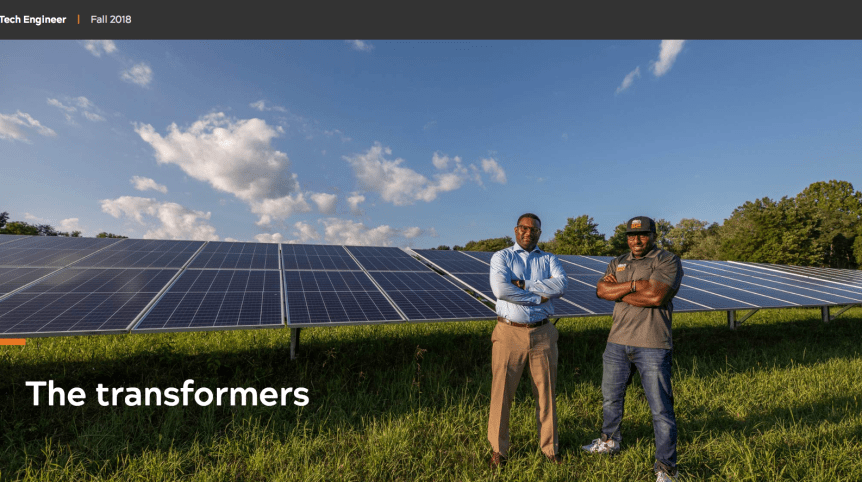 """Screenshot of a photo in which two men pose in front of solar panels in a field. The words """"The transformers"""" are written on top of the image."""
