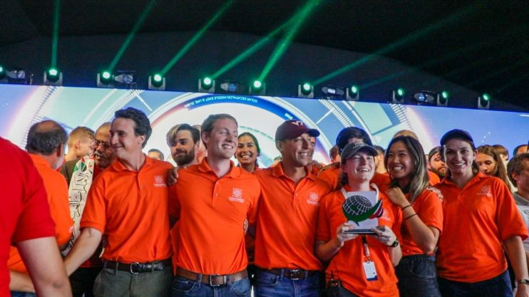 Students in orange team polos smile on a stage while one woman holds a trophy.