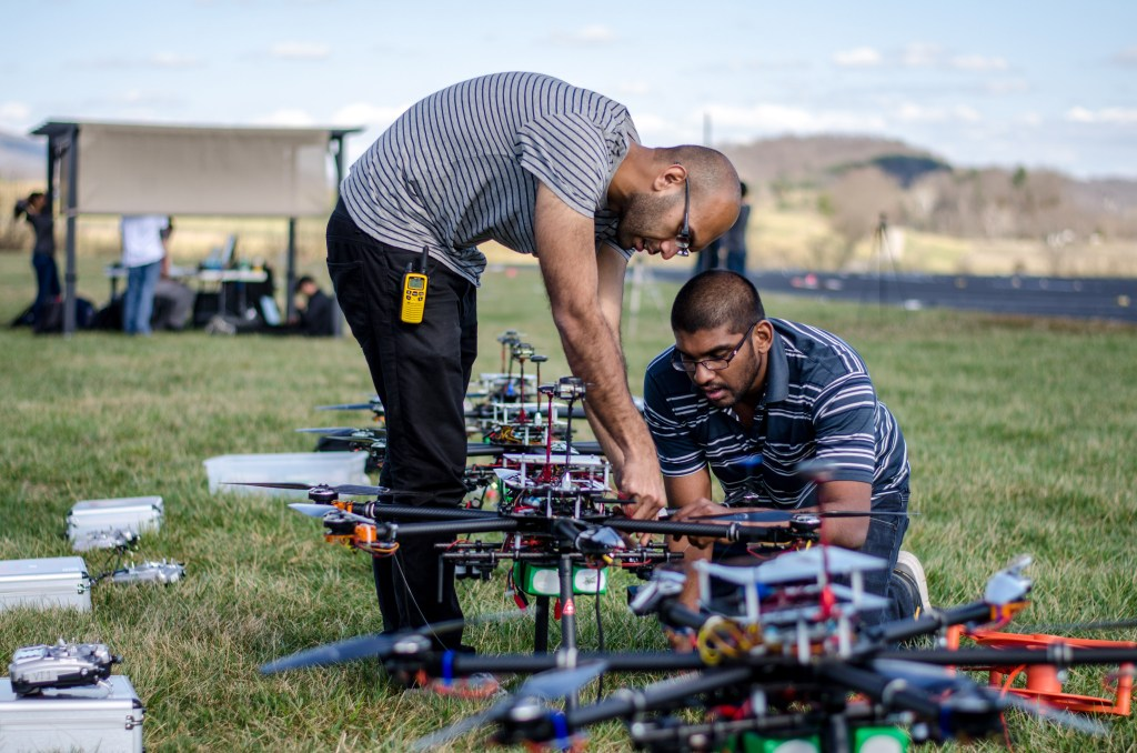 Two students adjust parts of a drone on the ground.