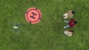 An overhead photo of three students flying a drone in a grassy field.