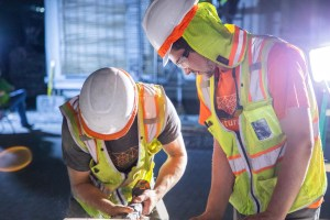 A photo of two people in safety gear on an active construction site using power tools.