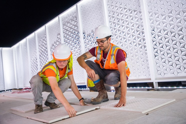 A photo of two people wearing safety gear and placing tiles on an active construction site in Dubai.
