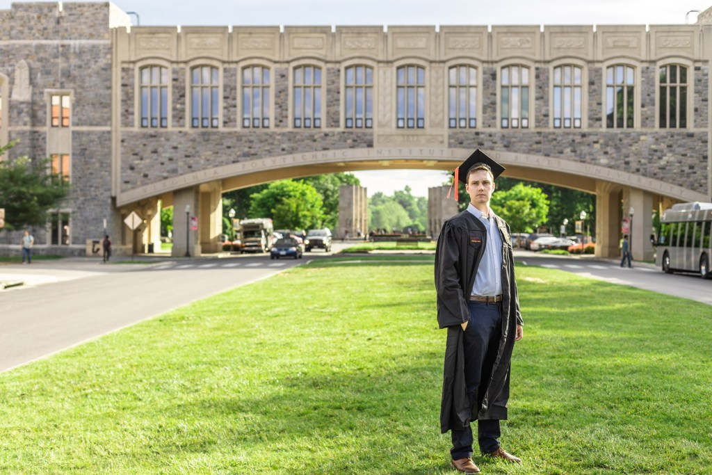 A photo of a graduate wearing a cap and gown and standing in front of an iconic bridge on the Virginia Tech campus.