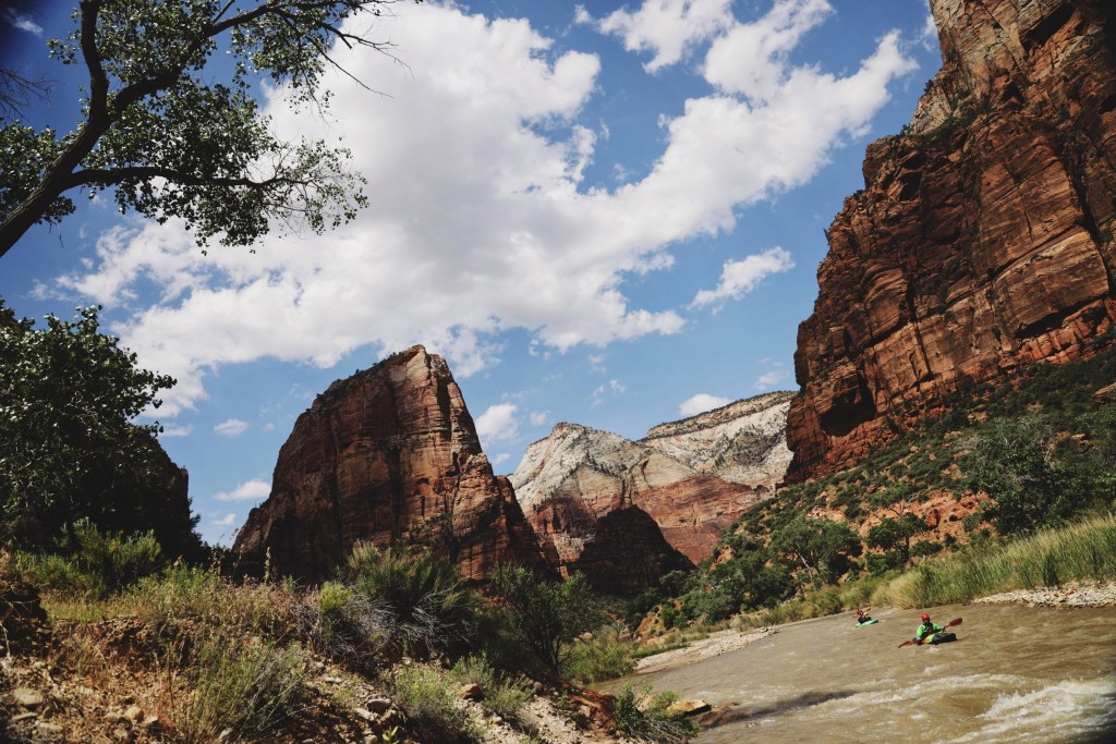 A photo of Zion National Park with the Virgin River flowing through it. Two kayakers are floating through the river.