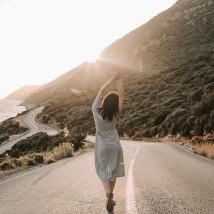 woman standing in the middle of a road feeling free