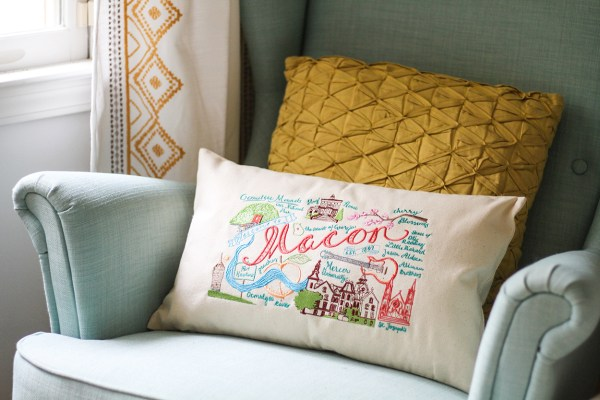 Macon Landmarks design colorfully embroidered on a pillow, sitting on an aqua armchair, Macon gift or souvenir