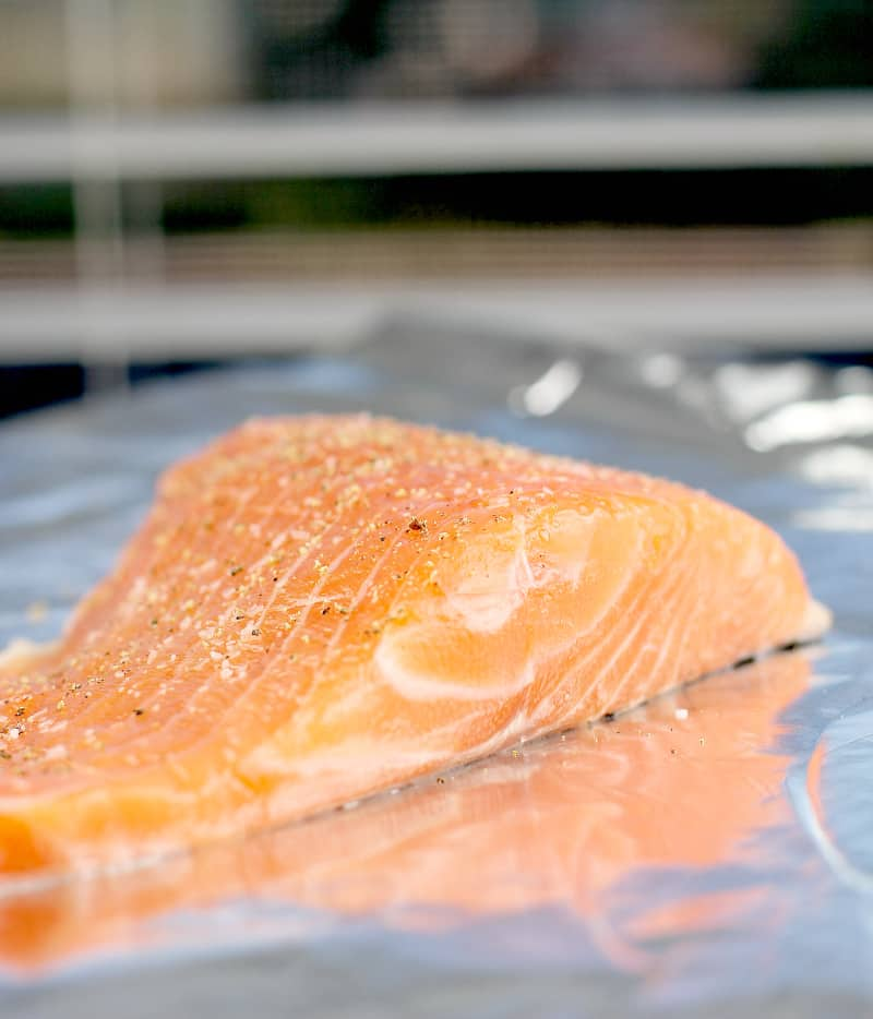 raw salmon on a bake sheet topped with salt and pepper