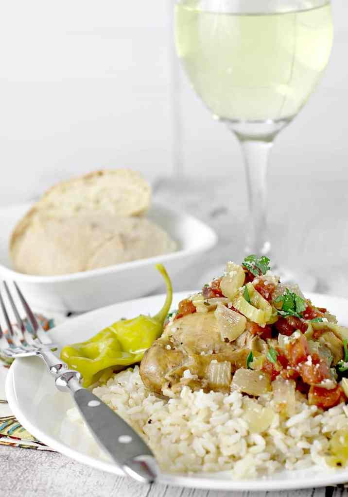 view showing cooked slow cooker italian pepperoncini chicken served over rice. Bread and glass of white wine are in the background.