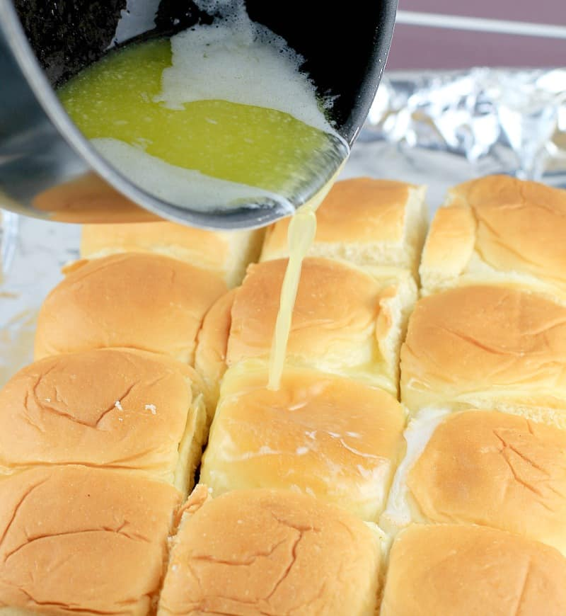 butter being poured over the Hawaiian roll turkey sliders